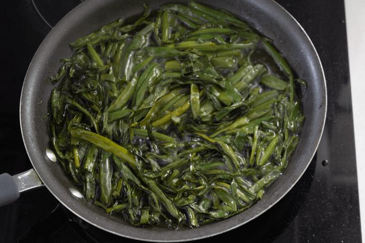 Scallions frying in a pan in oil.