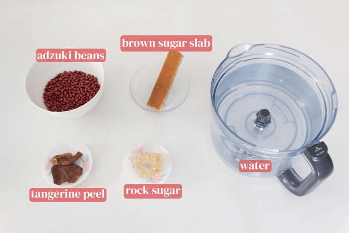 A food processor with water alongside bowls of adzuki beans and a brown sugar slab near dishes of rock sugar and tangerine peels.