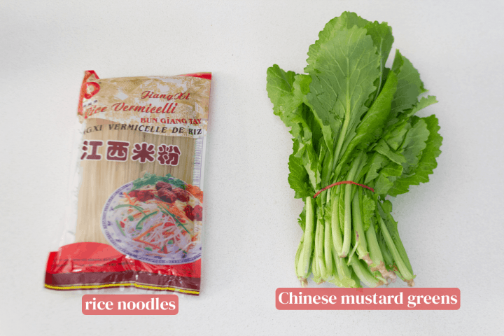 A packet of rice noodles and a bundle of Chinese mustard greens.