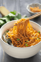 Chopsticks holding up Scallion Oil Noodles in a bowl.