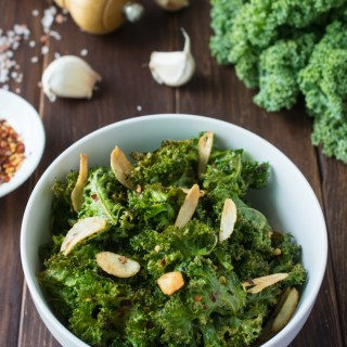 These healthy Spicy Garlic Kale Chips are irresistibly crispy and tasty! Fresh kale leaves are tossed in garlic oil and garlic powder, baked till crisp, then topped with crunchy garlic chips and spicy crushed red pepper.
