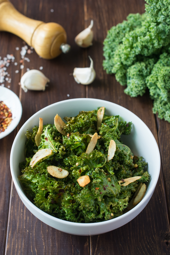 These healthy Spicy Garlic Kale Chips are irresistably crispy and tasty! Fresh kale leaves are tossed in garlic oil and garlic powder, baked till crisp, then topped with crunchy garlic chips and spicy crushed red pepper.