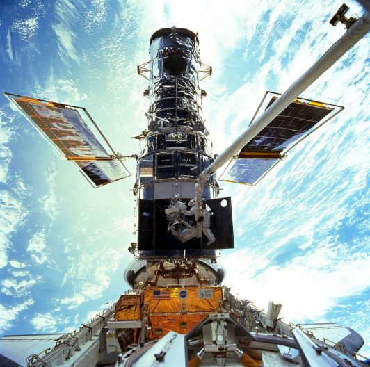 2 astronauts working on the Hubble Space Telescope, Earth in background.