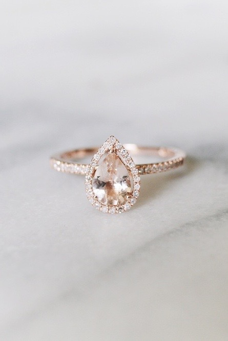A pear-shaped diamond engagement ring with halo diamonds sits on a marble table.
