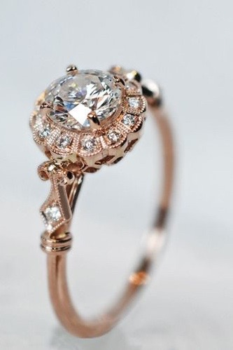 A vintage rose gold engagement ring with a diamond centre and an interesting, intricate diamond pattern surround.