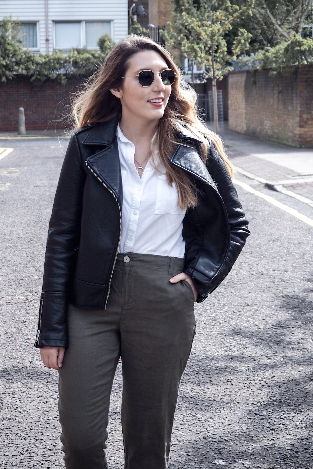 Woman walking down a London street wearing linen trousers, a white top and wearing a black leather jacket | Wolf & Stag