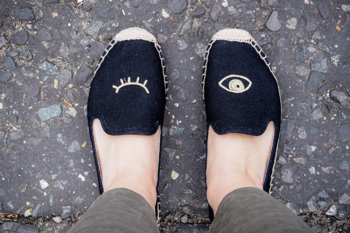 Two feet wearing winking eye black Soludos smoking slippers and the edge of linen trousers | Wolf & Stag