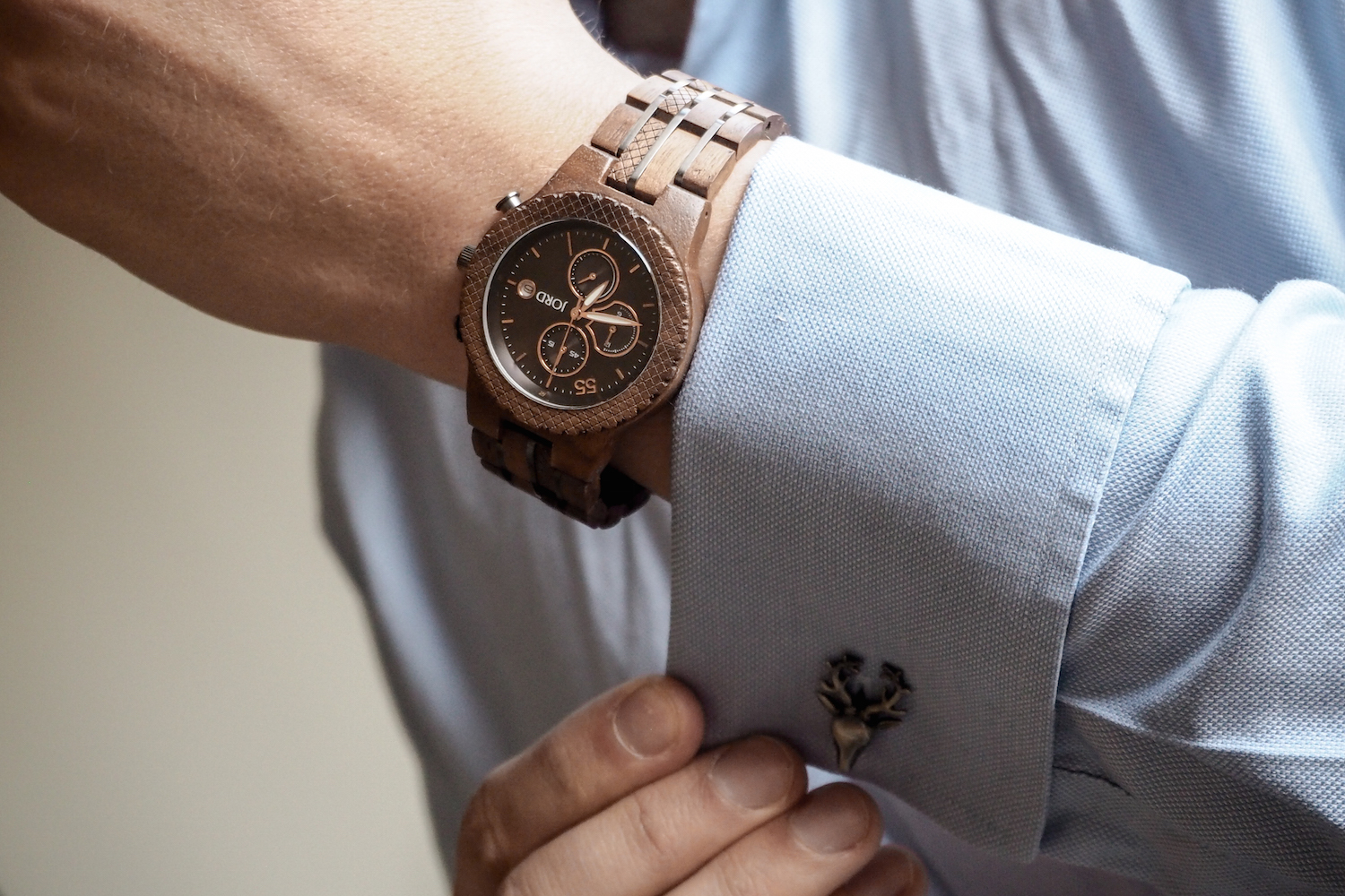 Man in blue shirt wearing wooden JORD Conway watch adjusts stag cufflinks