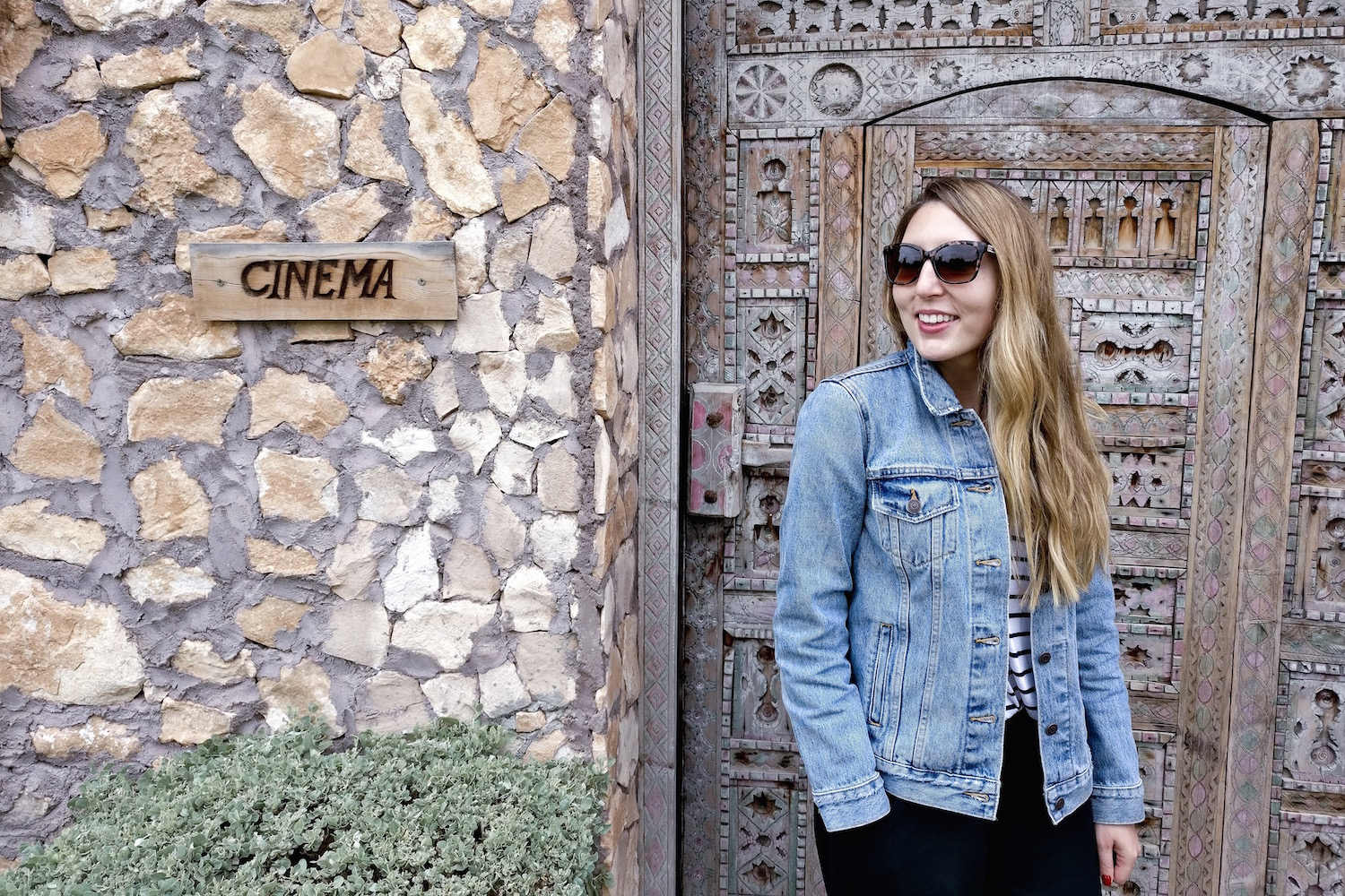 Eire Pollard wearing a Levi's denim jacket and Hush trousers stands outside the cinema room at Hotel Capaldi, Marrakech, Morocco | Wolf & Stag