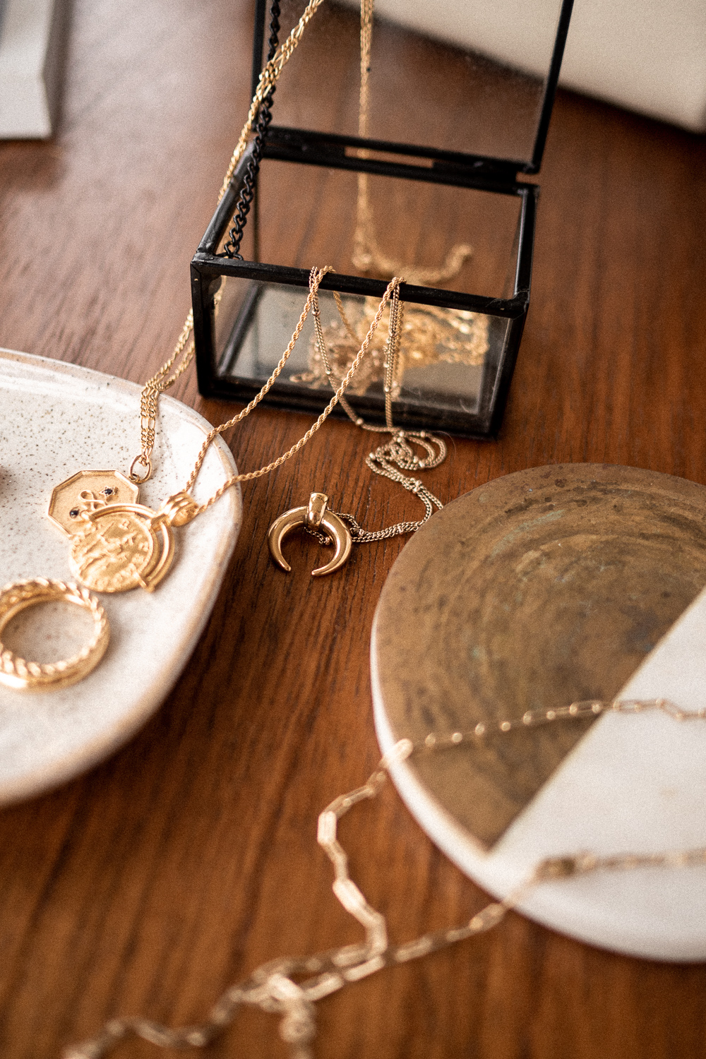 A close-up of gold necklaces, both pendant and chain, in my capsule jewelry collection