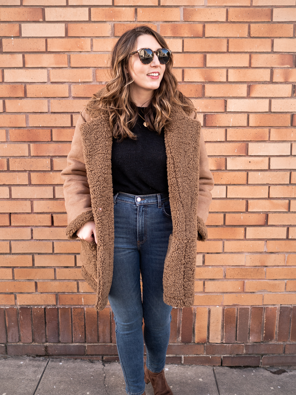 Blogger Erin wears the Reformation Barlow Coat in brown against a brown brick wall in San Francisco