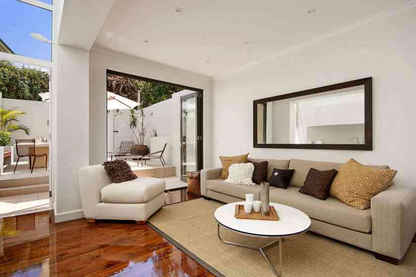outdoor-patio-with-bifold-doors-and-minimalist-living-room-furniture-plus-sisal-carpet-and-glossy-wood-flooring-with-wall-mirror