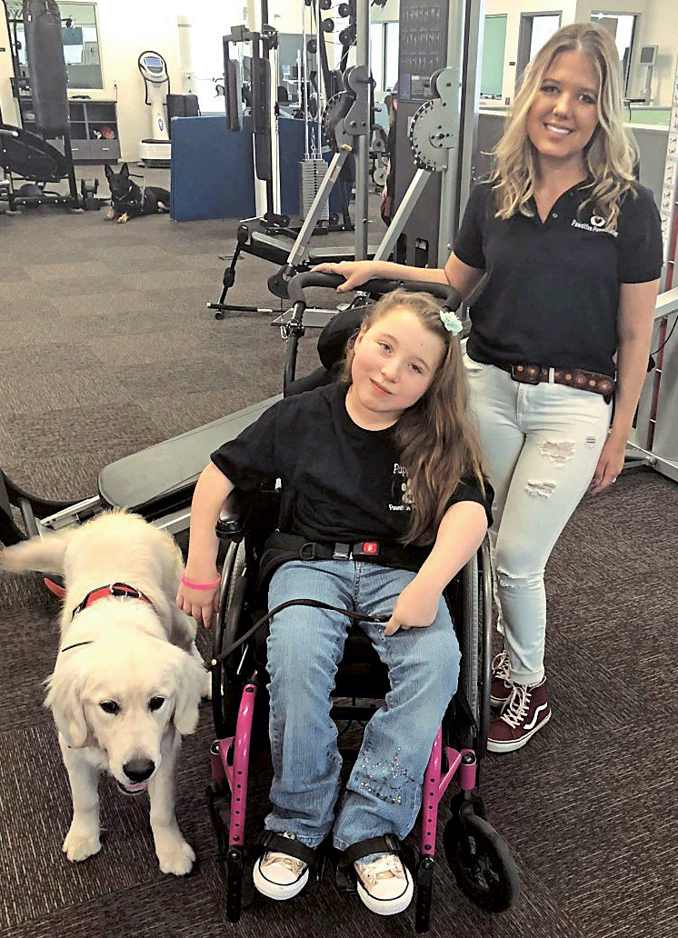 Eabha with her service dog, Tucker, and physical therapist