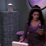 Troi in her office looking at a PADD