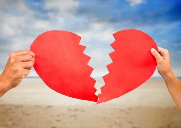Close-up of hands of couple holding broken heart on beach