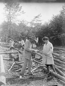 A member of the Women's Land Army Forestry Corps is assisted by a man in fixing an axe in the United Kingdom in 1914. Source: IWM Q 30697