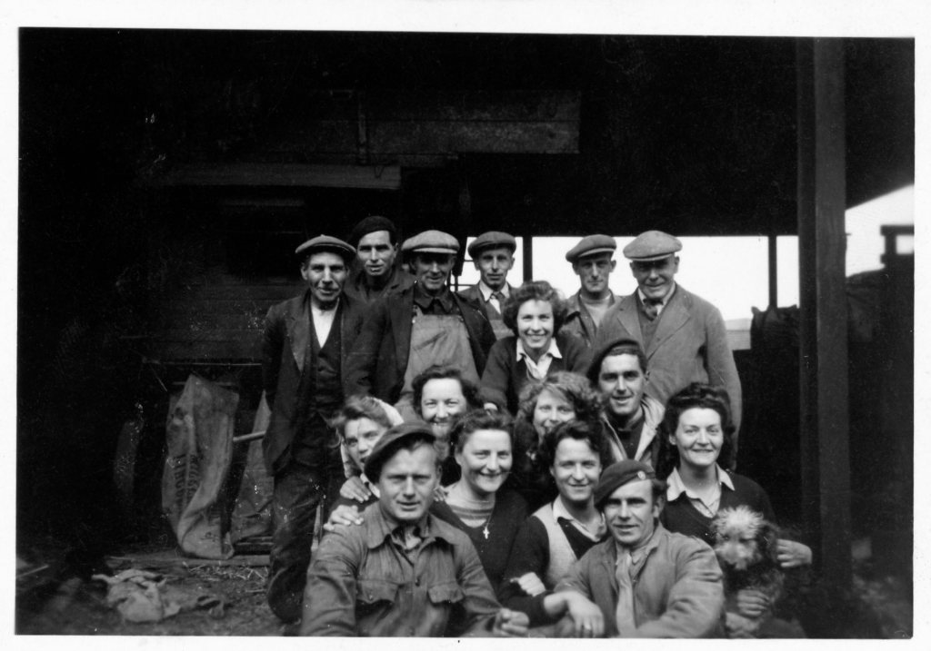 Group photo of farmers, Land Girls and two POWS on the front row