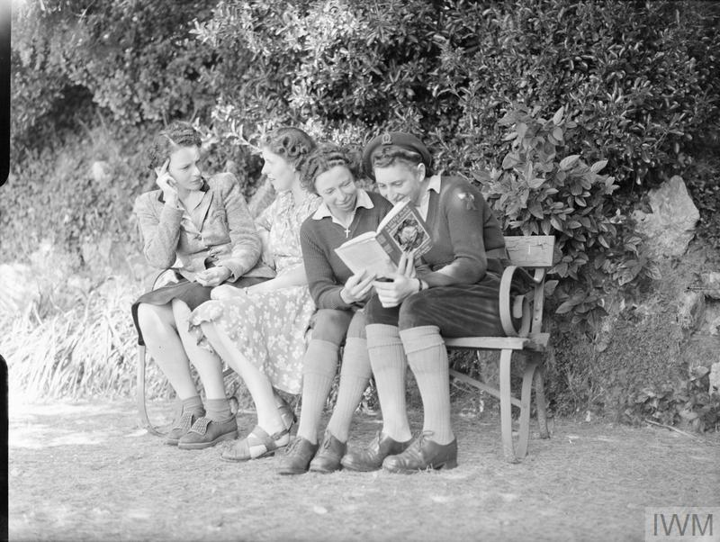 Enjoying a quiet spot on a bench under the trees in the garden of the rest break house in Torquay are (left to right) Mrs Eivemark (the forewoman of a WLA hostel), Miss Mary Pakes, Miss Ann Royne (WLA gang work forewoman) and Mrs Joan Hart (timber corps crane driver). Mrs Eivemark and Miss Pakes are chatting whilst Miss Royne and Miss Hart are reading a book together. Copyright: © IWM. Original Source: http://www.iwm.org.uk/collections/item/object/205200981