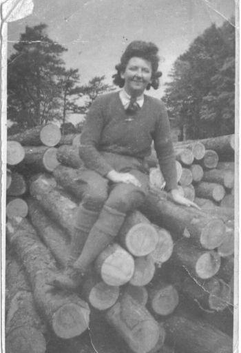 Gwyneth Mary Jones sitting on logs.