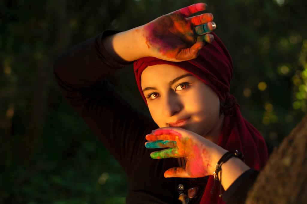 A hijabi woman, looking into the camera, has her paint-covered hands on her face.