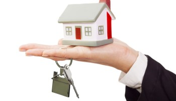 woman's hand holding keys and model of house
