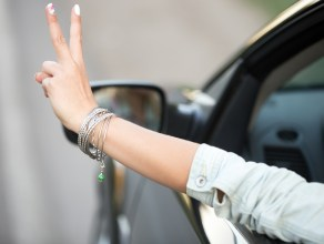 Beautiful young woman in casual denim jacket riding modern cabriolet car, showing victory gesture through the window, close up of hand with cute fashion bracelet, back view