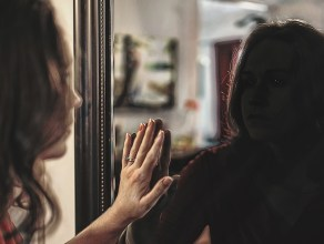 A woman looks at her reflection even though its dimly lit.
