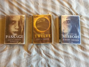 Three books of the passage trilogy on a striped brown bedspread starting the passage then the twelve then the city of mirors