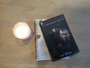paperback book 13 reasons why by Jay Asher on a notebook with a candle next to it