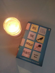 Paperback book All the bright places by jennifer niven next to a candle