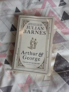 Arthur and George paperback by Julian Barnes on a white bedspread with pink and grey triangles