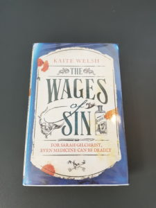 Hardback the wages of sin by Kaite Welsh on grey background
