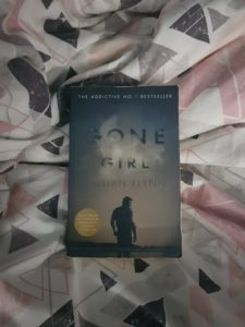 Book Gone Girl by Gillian Flynn on white duvet with grey and pink triangle pattern