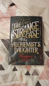 The Strange Case of the Alchemist's Daughter by Theodora Goss book on bedspread with grey and pink triangles