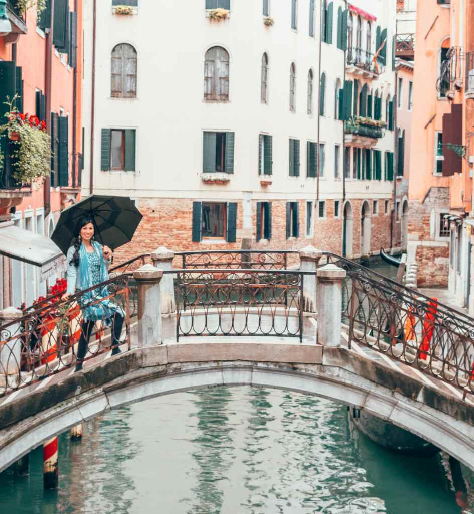 Woman with umbrella on bridge in venice wearing nomad's clothing UK