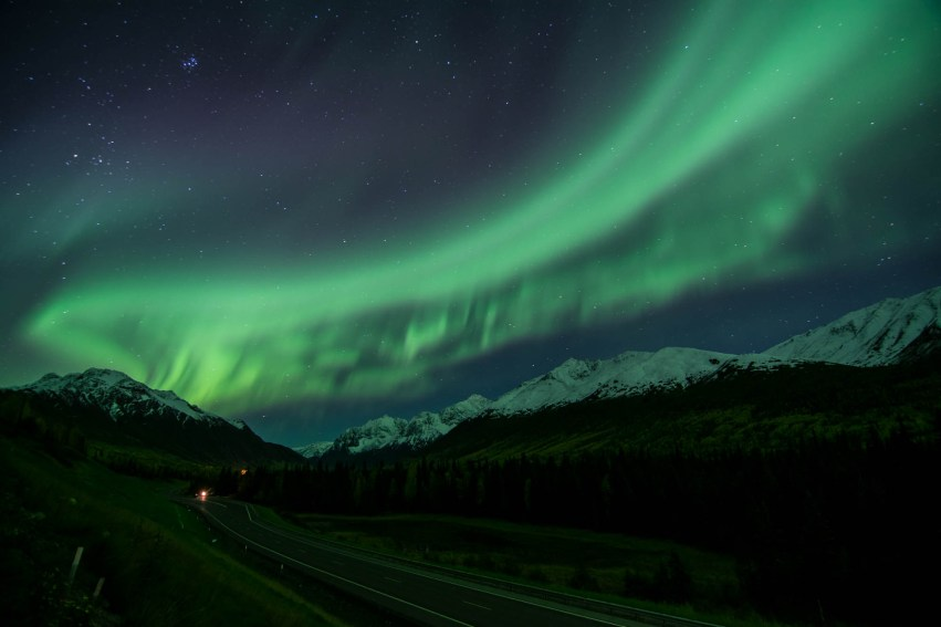 A long green band of northern lights hangs over a mountain road in Eagle river, Alaska. Stars are shining overhead. The mountains are capped with snow.