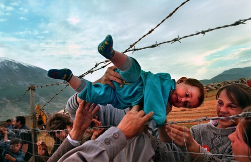 Agim Shala, 2 years old, is passed thru the barbed wire fence.