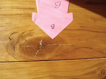 photo of checks originating from knot in wood floor