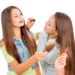 21563982 – pretty teenage girls applying make up and looking in the mirror