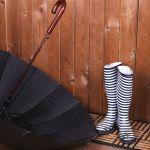 35884994 – dirty wellington boots with umbrella on door mat in room
