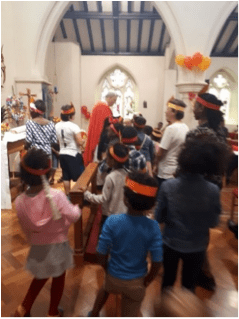 Children gathered around the alter in church