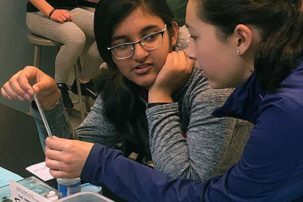 Two Middle School girls discuss an experiment in the chemistry lab.