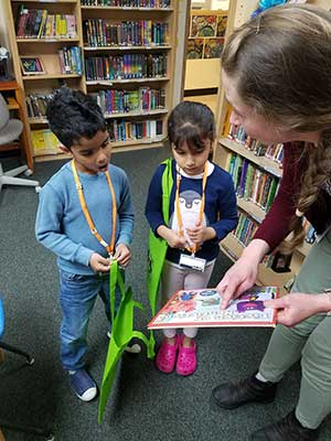 Two preschool students look at a book that the librarian is holding open for them. They have school totebags and they are in the library.