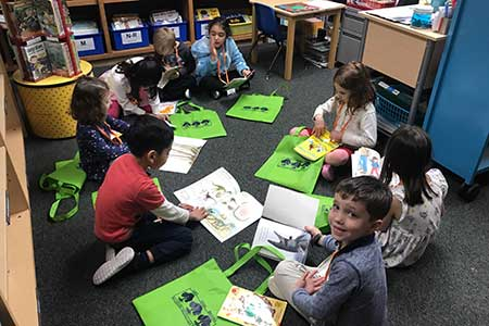 Kindergarten students in the library with tote bags and books