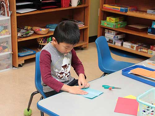 Folding paper airplanes at Winter Break Camp.