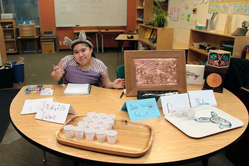 A student explains a Salish potlatch to visitors and offers smoked salmon samples.