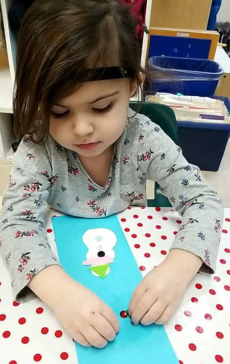 A preschool girl places red dots on a turquoise-colored sheet of paper