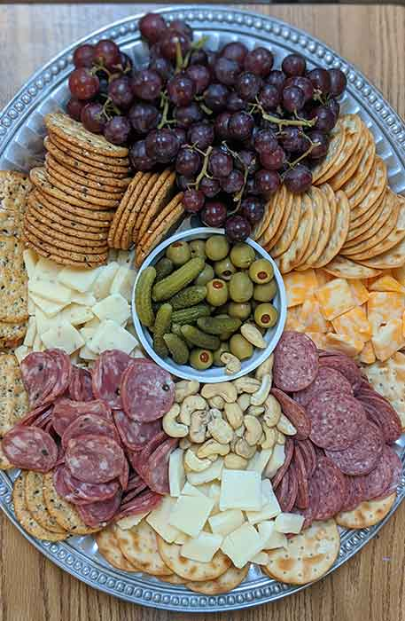 Sausage, cheese, crackers, nuts, olives, cornichon and grapes arranged on a platter