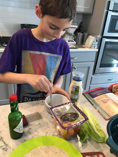 A boy stirs something in a bowl at a kitchen counter.
