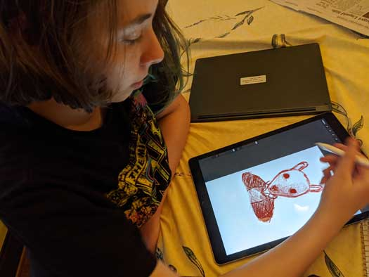 A Middle School girl draws using a digital tablet.